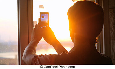 Young businessman taking picture with mobile phone against panoramic window  sunset city view