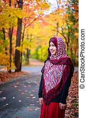 Muslim woman in Canada during autumn with colorful maple...