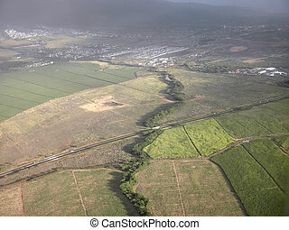 Aerial view of road passing through farmland fields and surrounding community in Maui, Hawaii.