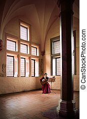 Woman playing guitar in Malbork Castle - A woman playing a...