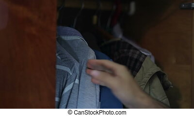 hand selects the shirt the closet