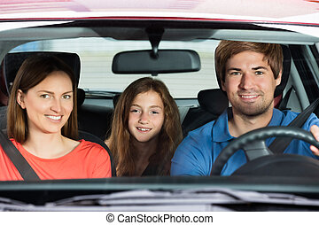 Couple Driving In Car With Their Daughter - Happy Young...