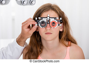 An Optometrist Checking Girl's Vision With Trial Frame