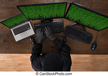 Robber Hacking Computers And Laptop - High Angle View Of...
