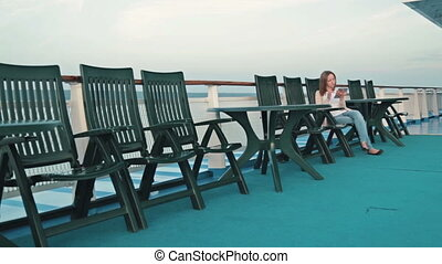 woman with pc digital tablet sitting on deck of cruise ship...