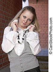 Portrait of Dreaming Caucasian Blond Woman in White Shirt Posing Against Brick Wall Outdoors.