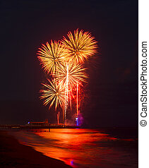 Fireworks in the sky reflected in seas at Bournemouth Pier -...