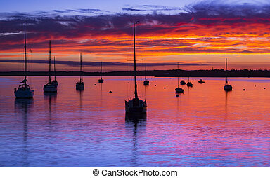The Sun sets over Poole Harbour in Dorset at Hamworthy pier...