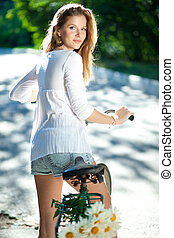 Woman and bicycle - Beautiful young woman in a white blouse...