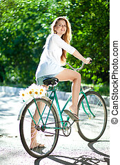 Woman and bicycle - Young woman in a white blouse and shorts...