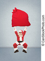 Santa Claus trains to lift very heavy bag with gifts, photo...