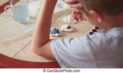 child paints the colors of plaster figures closeup - child...