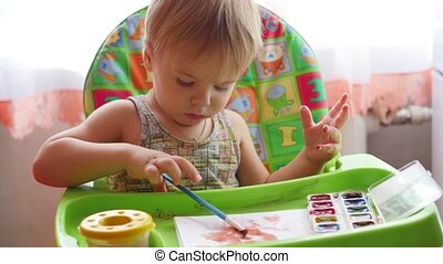 little child draws paints on a sheet of paper