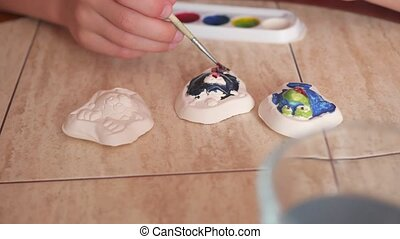 child paints the colors of plaster figures closeup