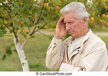 Sad elderly man outdoors