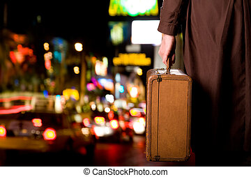 Leaving the city - A person with an old suitcase is standing...