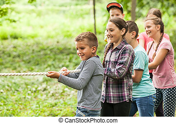 Tug-of-war in park - Group of happy smiling kids playing...
