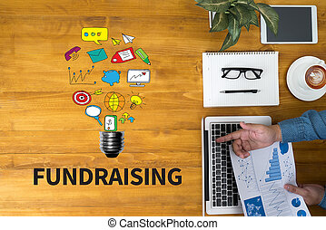 FUNDRAISING Businessman working at office desk and using...