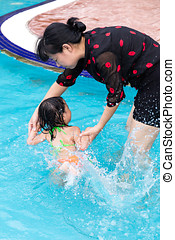 Asian Chinese Mom Teaching Little Girl Swimming At The Pool...