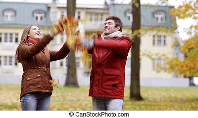 happy young couple throwing autumn leaves in park - love,...