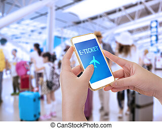 Hand holding smartphone with E-Ticket application for ticket reservation