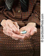 Senior woman holding assorted capsules in her hands.