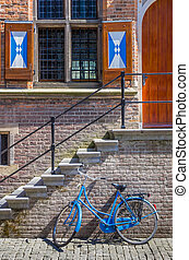 Blue bicycle in front of typical dutch building with blinds