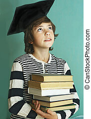 boy in graduation cap with book pile - preteen handsome boy...