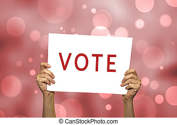 VOTE card in hand with abstract light background. Selective...