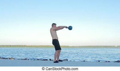 Man raises dumbbell, trained athlete, the athlete on the...