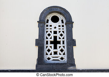 An old prison window with a stone wall grille with a cross...