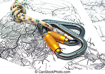 two alpinism carabiners on a map background - two alpinism...