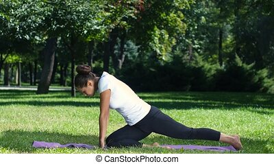 Woman working out doing a stretch exercise in the park on a yoga mat