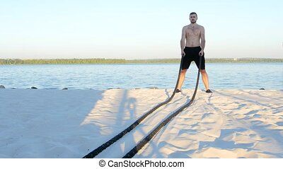 Battle ropes on the river bank, trained athlete, battle...