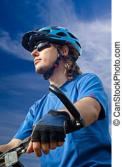 young biker in helmet on a blue sky background