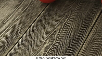 Tomatoes roll over the screen in slow motion on wooden...