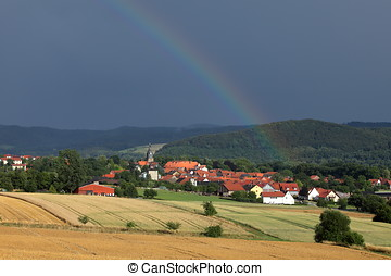 The village of Herleshausen with a rainbow after a summer...