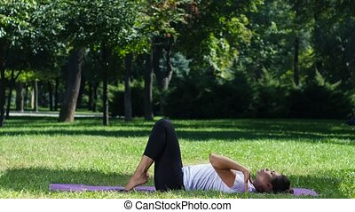 Women practicing yoga in the park background, exercising in...