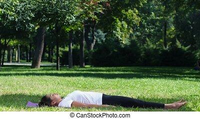 Woman practicing yoga in the park - Women practicing yoga in...
