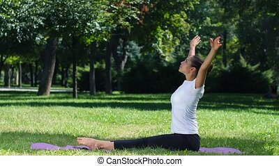 Girl with a sports figure is engaged in yoga in park, oman...
