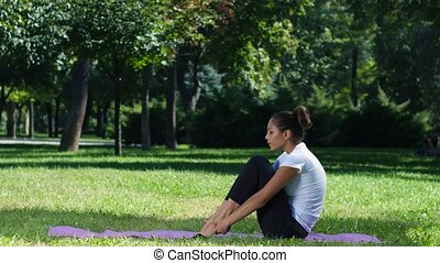 Girl is doing yoga in park, girl with a sports figure is...