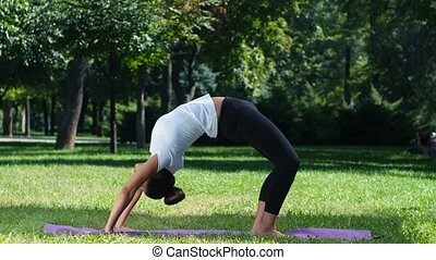 Girl is engaged in yoga, outdoors in a park in summer, women...