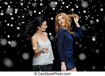happy young women dancing over snow - new year party,...