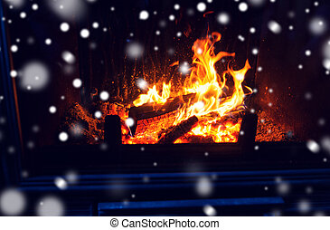 close up of firewood burning in fireplace and snow - winter,...
