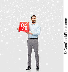 smiling man with red percentage sign over snow - people,...