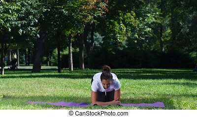 Fit girl doing yoga in the park on a sunny day, woman...