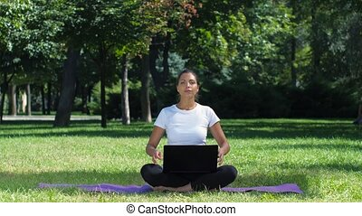 Woman working with laptop sitting lotus pose. Yoga - Woman...