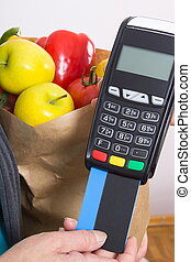 Hand of senior woman using payment terminal with credit...