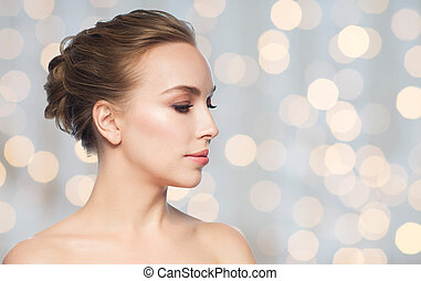 beautiful young woman face over holidays lights - health,...