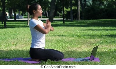 Young woman yoga in the park working on a laptop. Lotus pose...